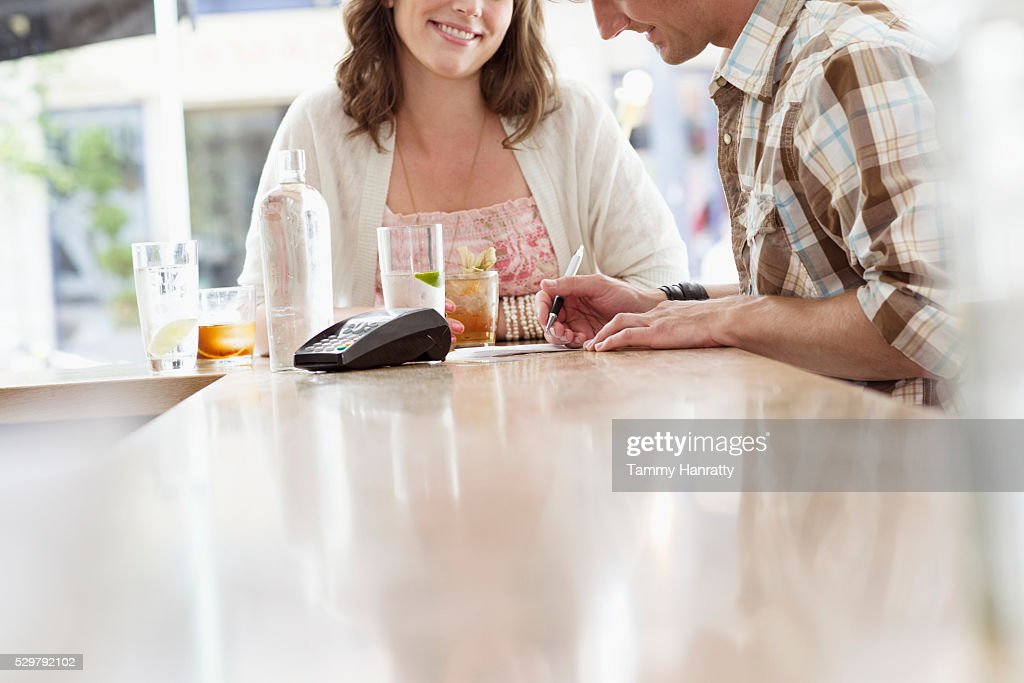 Mid adult man paying bill in bar : Stock-Foto