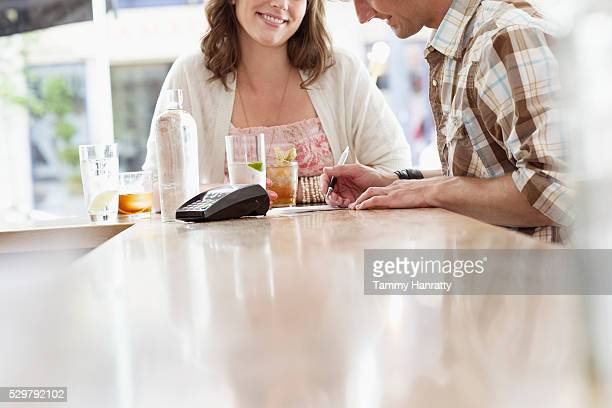 mid adult man paying bill in bar - tammy bar stock pictures, royalty-free photos & images