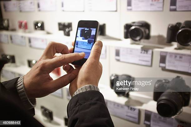 mid adult man photographing camera's in shop display using smartphone - electronics store stock photos and pictures
