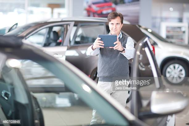 Mid adult man photographing car in showroom