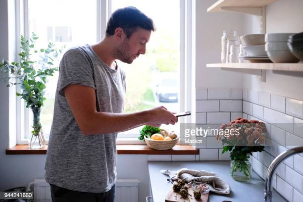 mid adult man photographing food through smart phone at kitchen counter - photo messaging stock pictures, royalty-free photos & images