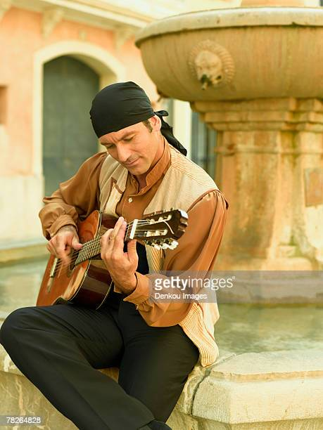 mid adult man playing a guitar and looking down - flamenco stock photos and pictures