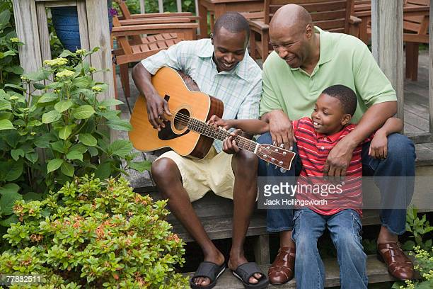 Mid adult man playing a guitar with his father and his son sitting beside him
