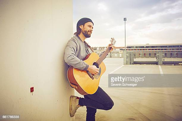 Mid adult man playing acoustic guitar on rooftop parking lot