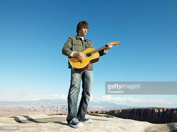 Mid adult man playing acoustic guitar, rock strata in background, low angle view