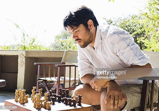 Mid adult man playing chess at safari lodge, Kafue National Park, Zambia