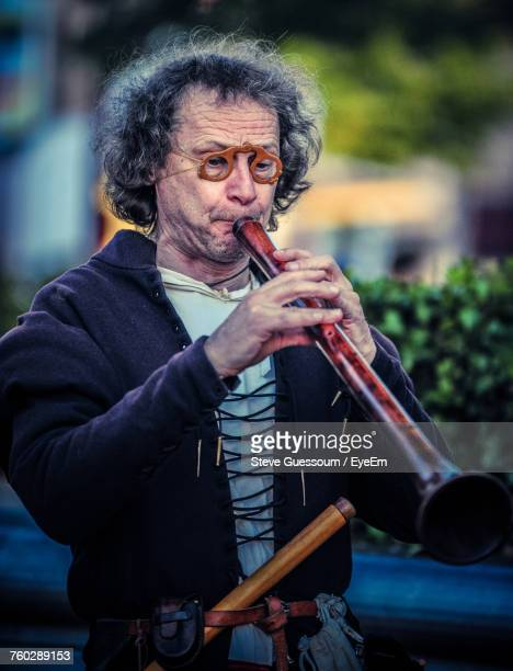 mid adult man playing flute - steve guessoum stockfoto's en -beelden