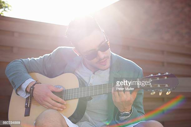 Mid adult man playing guitar at rooftop party