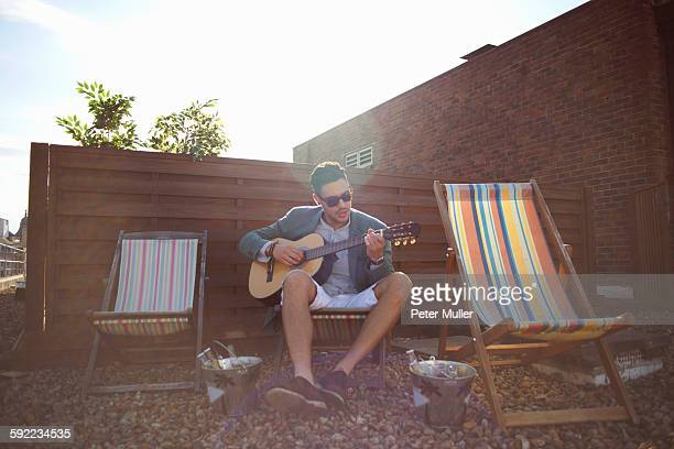 mid adult man playing guitar on deckchair at rooftop party - only mid adult men stock pictures, royalty-free photos & images
