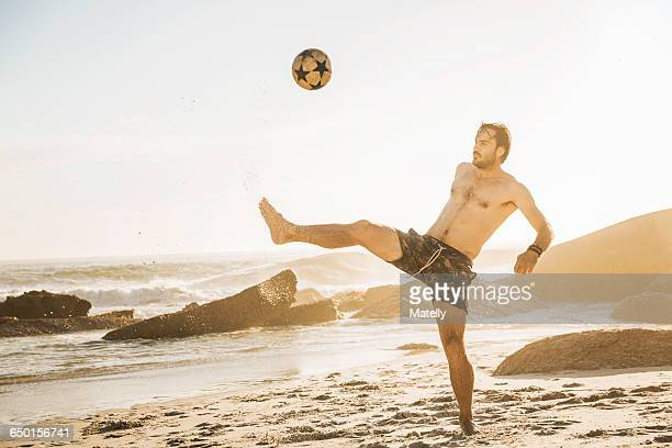 Mid adult man playing soccer keepy uppy on beach, Cape Town, South Africa