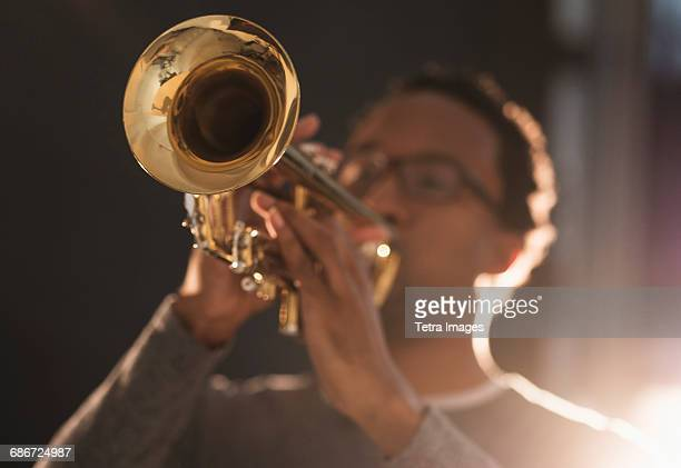 mid adult man playing trumpet - trumpet stock pictures, royalty-free photos & images