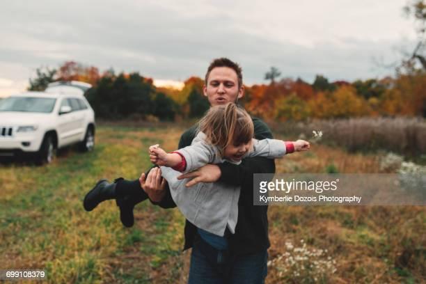 mid adult man playing with toddler daughter in field - wildpflanze stock-fotos und bilder