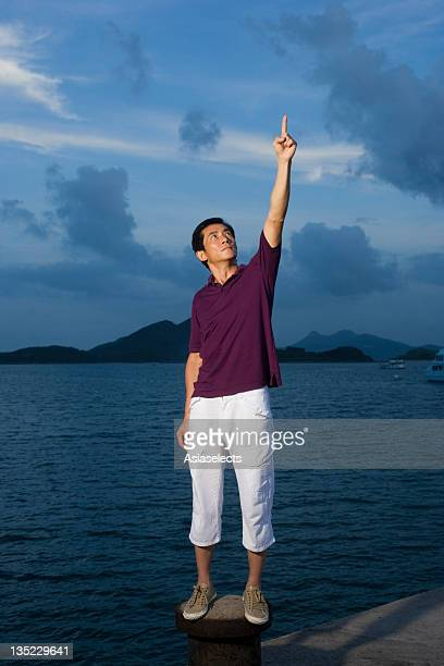 Mid adult man pointing upwards on the beach