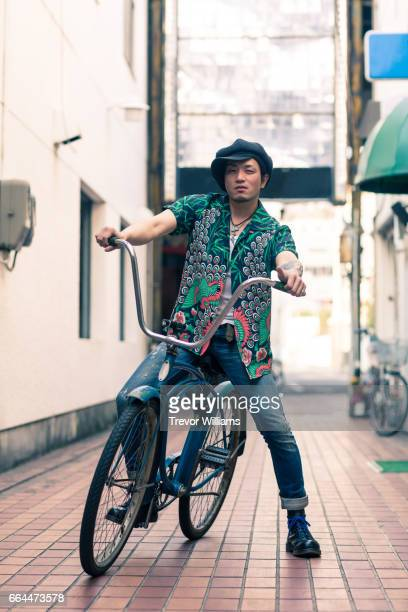 Mid adult man posing on a retro styled vintage bicycle