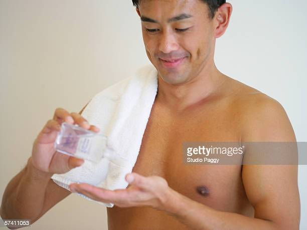 Mid adult man pouring after shave lotion on his hand