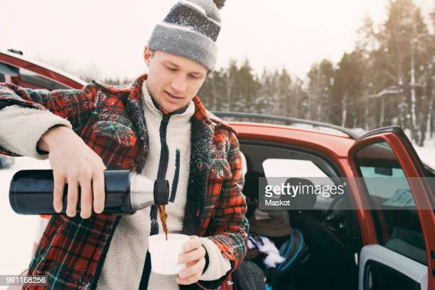 mid adult man pouring coffee from insulated drink container while standing by car - flask stock pictures, royalty-free photos & images