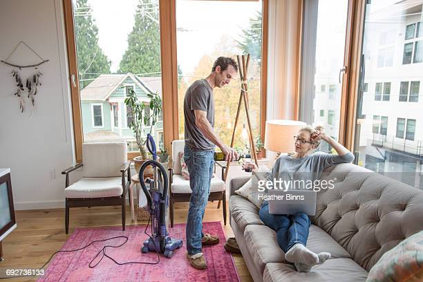 mid adult man pouring red wine for girlfriend reclining on sofa - role reversal stock photos and pictures