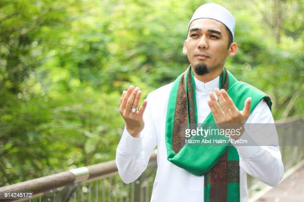 mid adult man praying while standing by railing at park - allah photos et images de collection