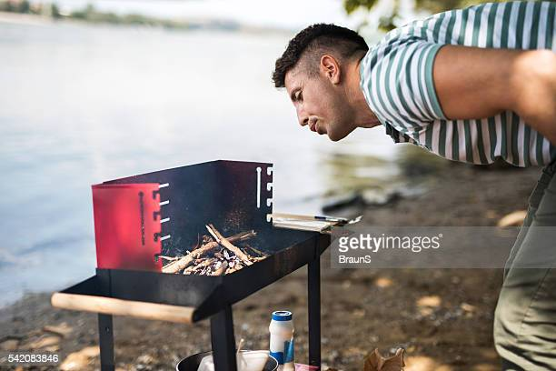 Mid adult man preparing fire for the barbecue.