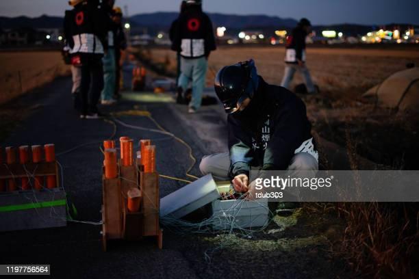 お祝いのイベントやフェスティバルの準備のために花火を準備するミッドアダルト男性 - explosive material ストックフォトと画像