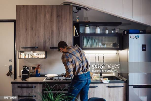 mid adult man preparing food at kitchen hob, rear view - burner stove top stock pictures, royalty-free photos & images