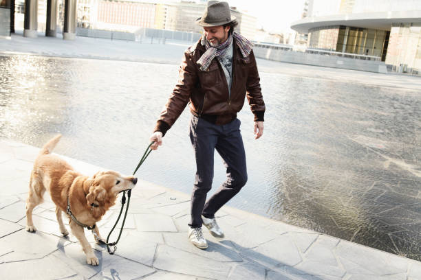 Mid adult man pulling leash on pet dog in city