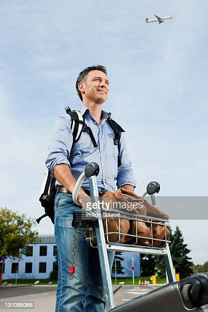 Mid adult man pushing luggage trolley at airport