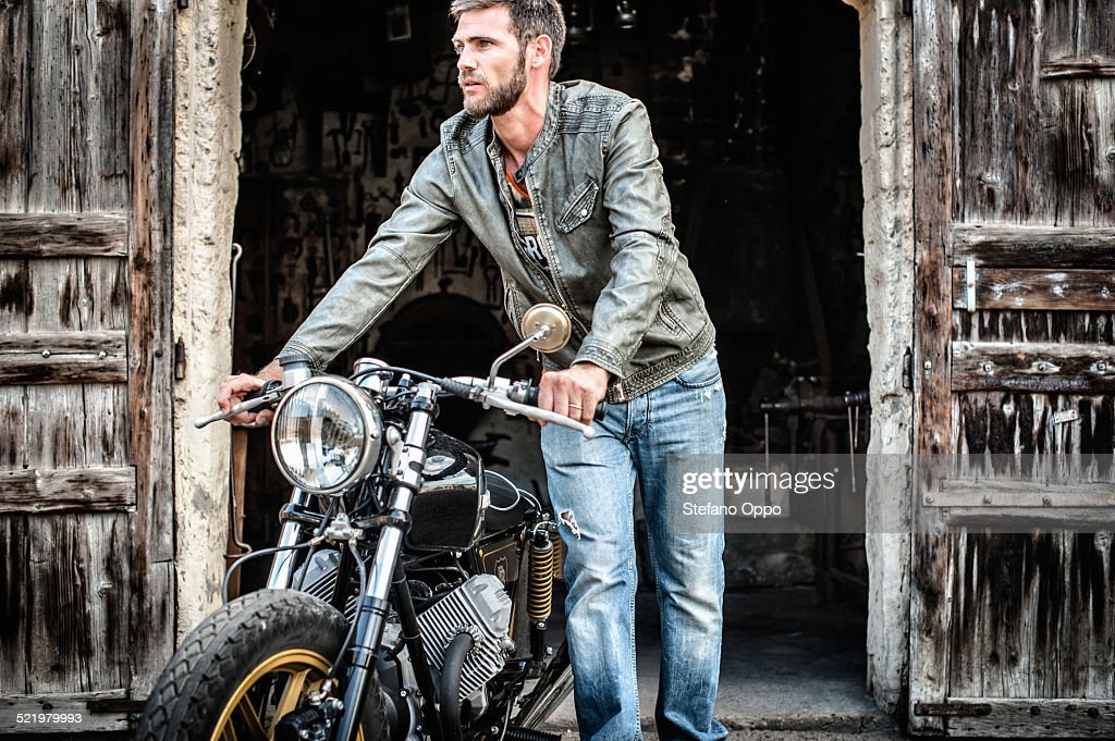 Mid adult man pushing motorcycle out of barn : Stock Photo