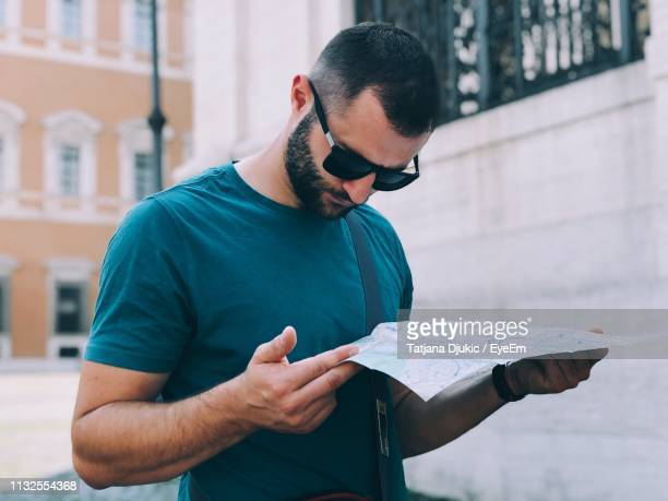 mid adult man reading map while standing against buildings in city - mid volwassen mannen stockfoto's en -beelden
