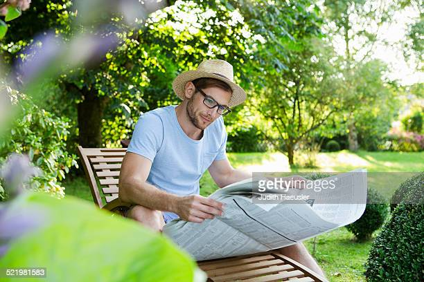 Mid adult man reading newspaper in garden