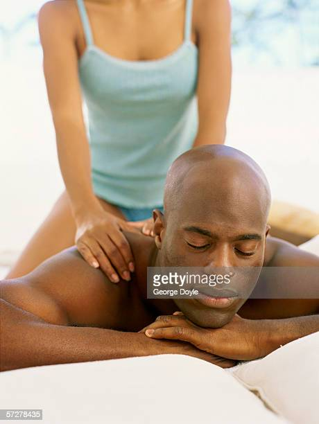 Mid adult man receiving a back massage from a woman