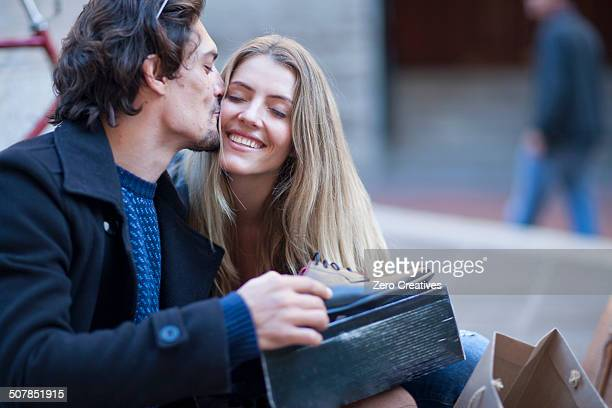 Mid adult man receiving gift of shoes from girlfriend on city street