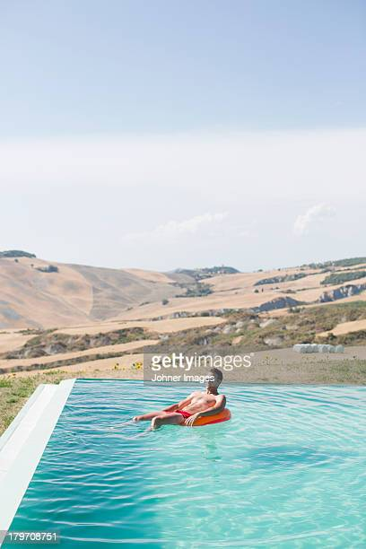 Mid adult man relaxing in swimming pool
