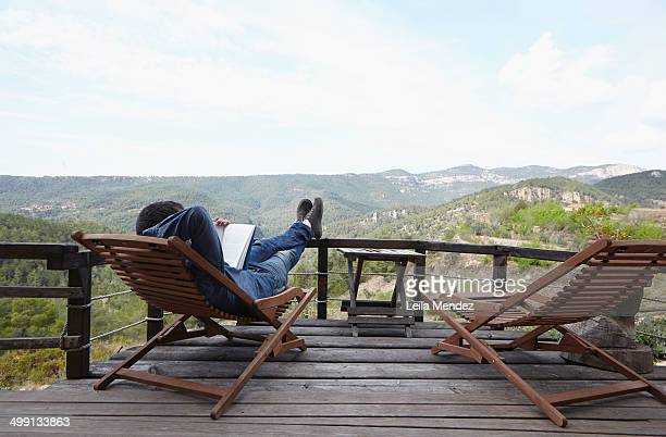Mid adult man relaxing with book on balcony, Villahermosa del Ri¡o, Castellon, Spain