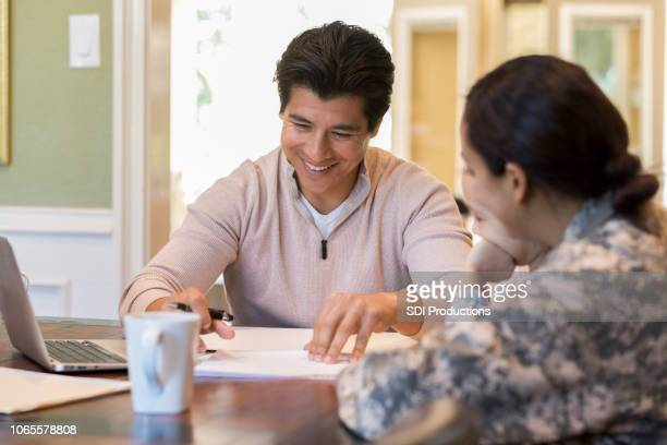 mid adult man reviews document with army wife - military spouse stock pictures, royalty-free photos & images