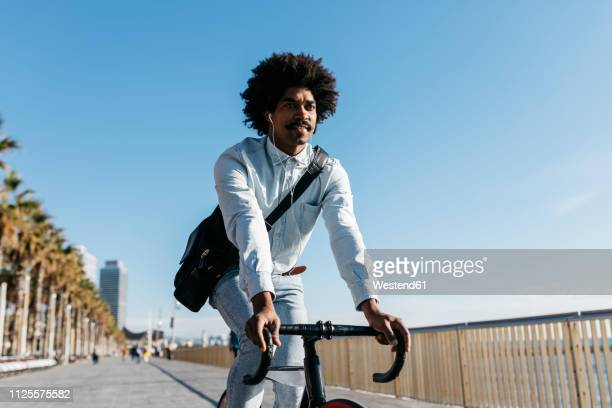 mid adult man riding bicykle on a beach promenade, listening music - commuter stock pictures, royalty-free photos & images