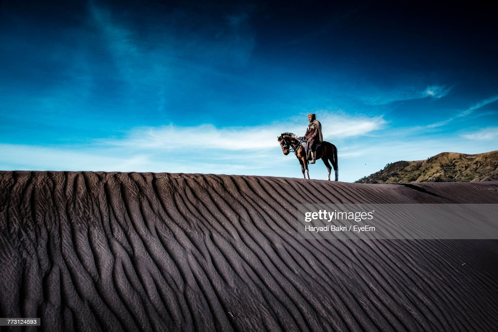Mid Adult Man Riding Horse On Sand At Desert Against Sky : Photo