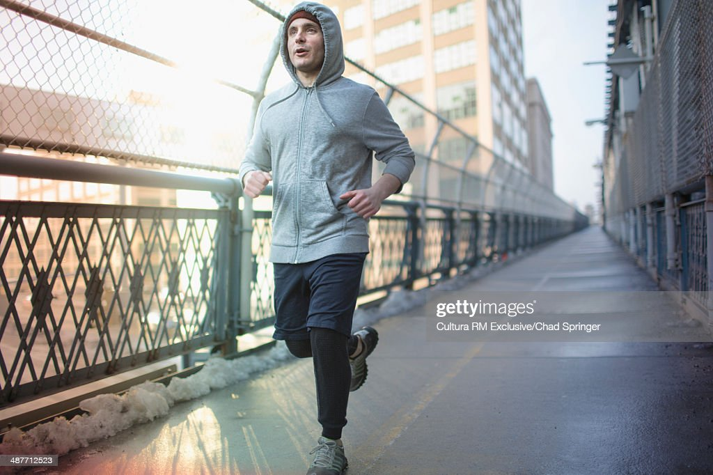 Mid adult man running across bridge : Stock Photo