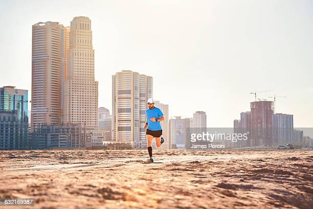 Mid adult man running on sand by skyscrapers, Dubai, United Arab Emirates