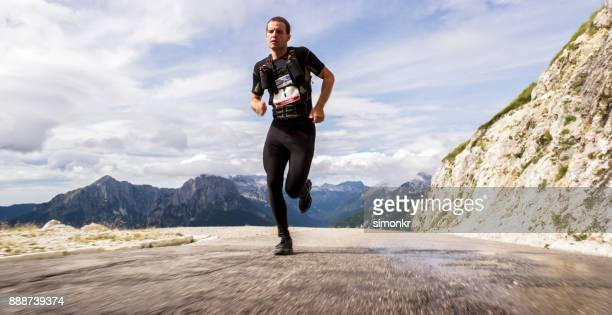 Mid adult man running up high mountain road with mountain peaks in background