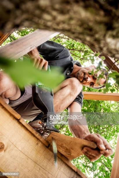 Mitte erwachsenen Mannes Sägen ein Holzbrett