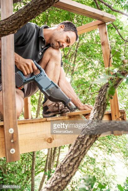Mid adult Man Sawing a Wooden Plank