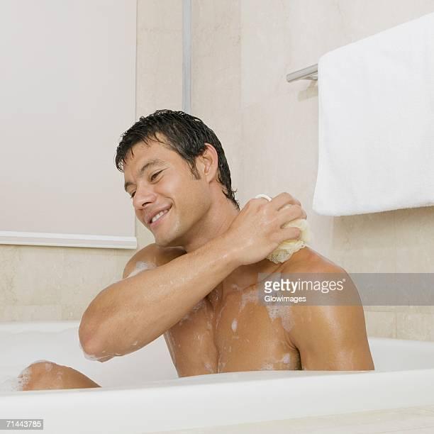 Mid adult man scrubbing his body in the bathtub