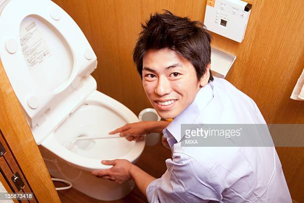 Mid adult man scrubbing toilet bowl