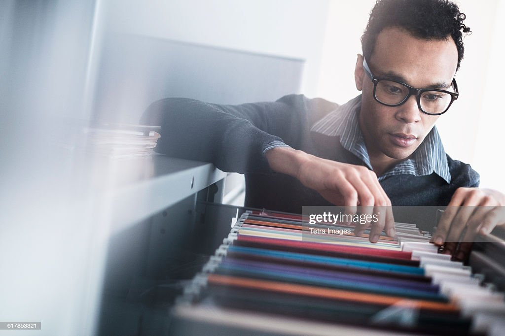 Mid adult man searching for files in filing cabinet : Stock Photo