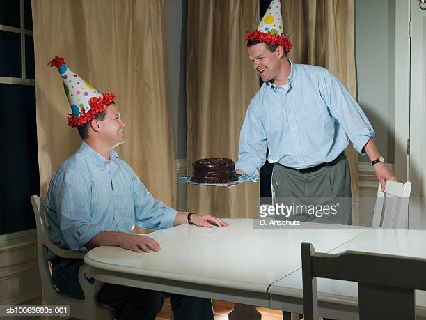 Mid adult man serving birthday cake to twin brother, digital composite