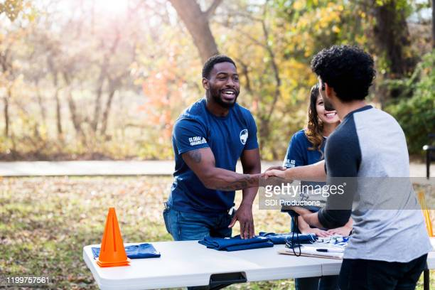 mid adult man shakes hands with unrecognizable volunteer - non profit organization stock pictures, royalty-free photos & images