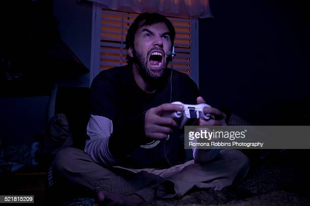 mid adult man shouting whilst playing video game at night - gamer stock pictures, royalty-free photos & images