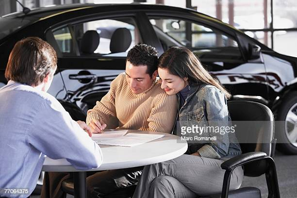 Mid adult man signing a document with a young woman sitting beside him in front of a car salesman