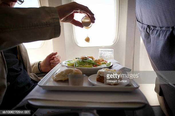 Mid adult man sitting at airplane, adding mustard to salad